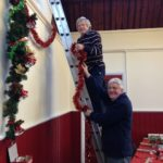 Graham and Mike hanging Xmas decorations